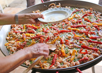 hand of the chef adds shrimp in rice paella with seafood