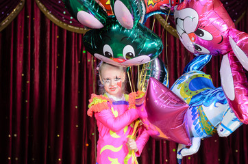 Girl in Costume Holding Bunch of Balloons on Stage