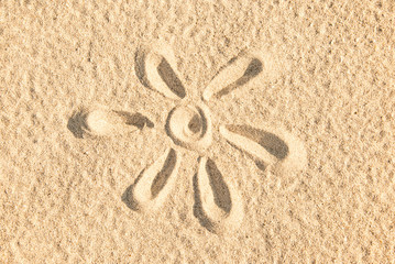 Close up of a sun sketched in the sand of a beach