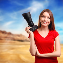 Young female photographer taking photos on nature background