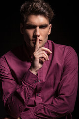 casual man making the silence gesture