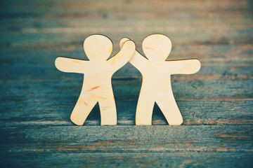 Wooden little men holding hands on wooden boards background. Sym