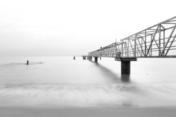 Black and white long exposure photo of steel jetty leading to the ocean.