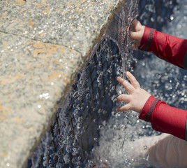 A baby explores water in a fountain for the first time
