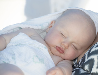 A beautiful baby boy sleeps on the beach in Cancun, Mexico