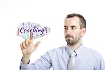 """Young businessman touching """"Coaching"""" word cloud"""
