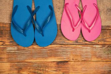 Wooden grunge background with two paar flip flop sandals
