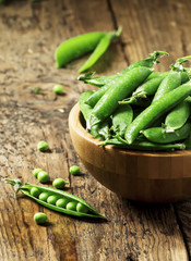 Pods of fresh green peas in a bowl on old wooden table, selectiv