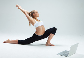 Girl makes yoga exercise online with laptop