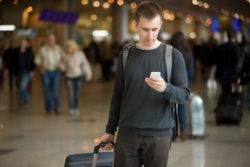 Young traveler using mobile phone in airport
