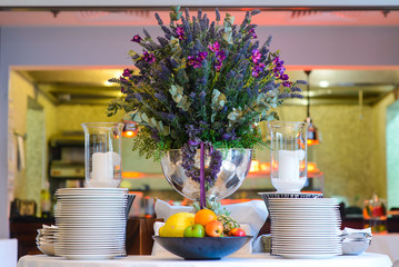 A huge vase of flowers on decorated table in the restaurant.