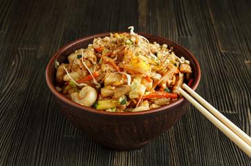 Pad thai with chopsticks on wood close-up