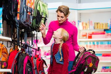 Mutter und Kind kaufen Schulranzen im Geschäft