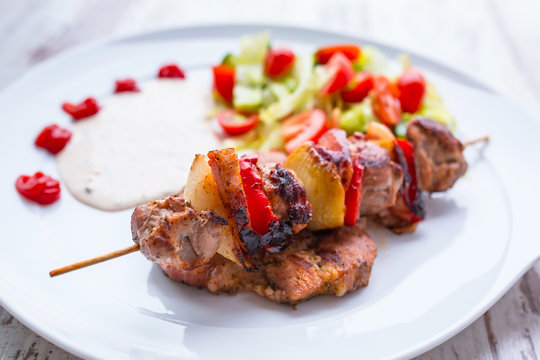 Grilled duck shashlik with salad on the plate