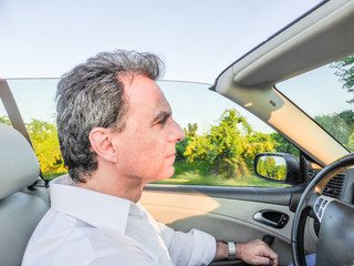 Handsome middle-aged man driving convertible car