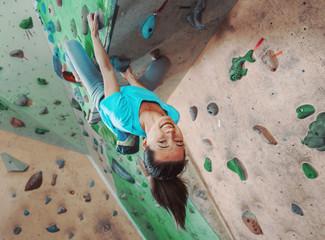 Happy sportswoman climbing indoor