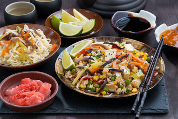 asian lunch - fried rice with tofu and vegetables on dark table
