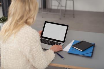 frau im büro schaut auf ihren laptop