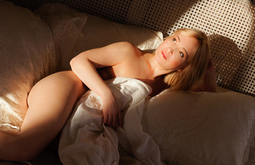 Half-naked woman in bed in the sunlight