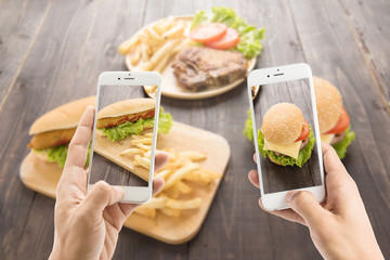 Friends using smartphones to take photos of hot dog and hamburge