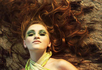 beautiful young woman face with make-up and long red hair on the beach