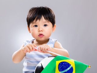 Baby boy hold with soccer ball and Brazil flag