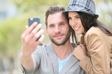 Cheerful young couple taking selfie picture with smartphone