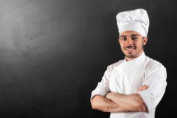 cuoco sorridente su fondo lavagna nero