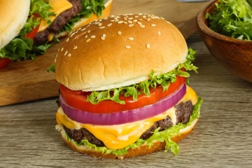 Cheese burger with lettuce and tomatoes close up on wooden background