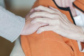 Frau haelt Hand auf der Schulter einer Seniorin
