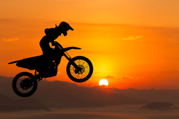 silhouette of biker jumping