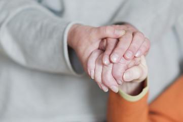 Frau haelt Hand von einer Seniorin