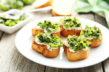 Tasty fresh bruschetta on plate on grey wooden background