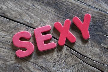mot sexy en lettres rouge fond de bois