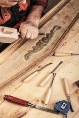 Senior carpenter restoring old furniture in his workshop