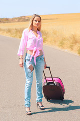 young woman with suitcase walking along the road