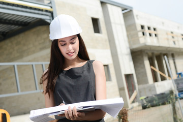 woman architect supervising building construction site with blueprint