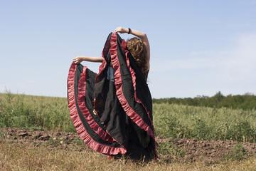 Young woman dancing outdoors in long skirt