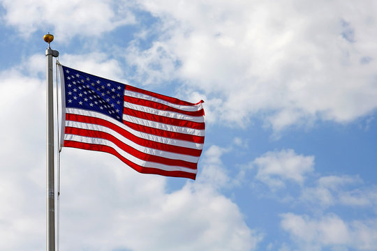 American Flag in front of Cloudy Blue Sky