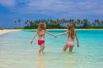 Adorable happy little girls have fun at shallow water on beach