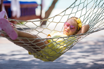 Little girl on tropical vacation relaxing in hammock