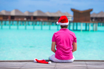 Young man in santa hat during beach vacation on wooden jetty