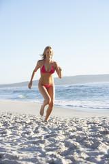 Young Woman Running Along Sandy Beach On Holiday Wearing Bikini