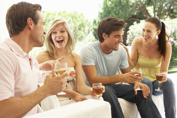 Group Of Young Friends Relaxing On Sofa Drinking Wine Together