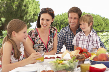 Young Family Enjoying Outdoor Meal Together