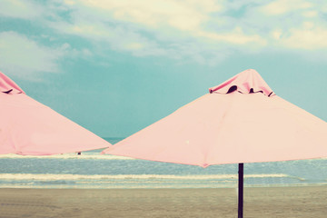 Retro beach with pink umbrellas
