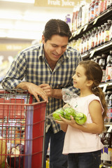 Father and daughter buying fruit in supermarket