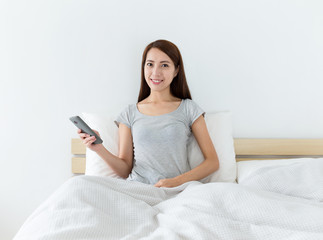 Asian woman holding the mobile phone and sitting on the bed