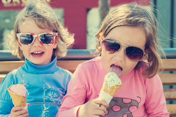 Two little girls eating ice cream.