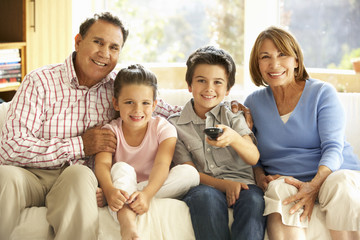 Hispanic Grandparents With Grandchildren Watching TV On Sofa At Home